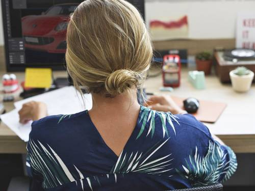 Junge Frau sitzt an einem Schreibtisch