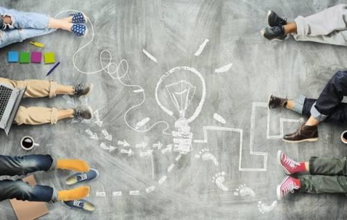 Ein Symbolbild: Füße von Kindern um eine mit Kreide gemalte Glühbirne
