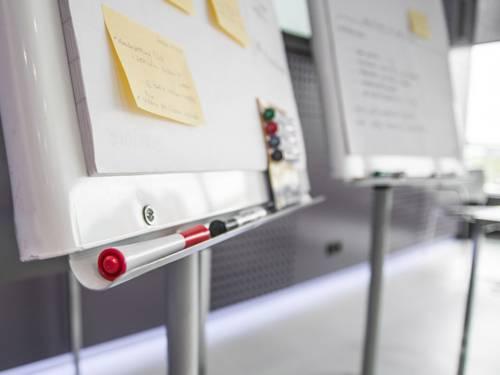 Zwei Flipcharts mit beschriebenen Post-Its und Stiften