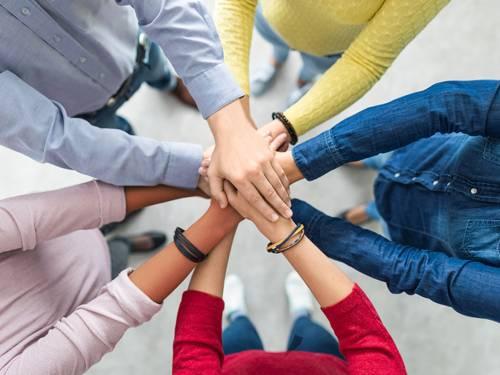 Fünf Menschen stehen im Kreis und haben die Hände übereinander gelegt.