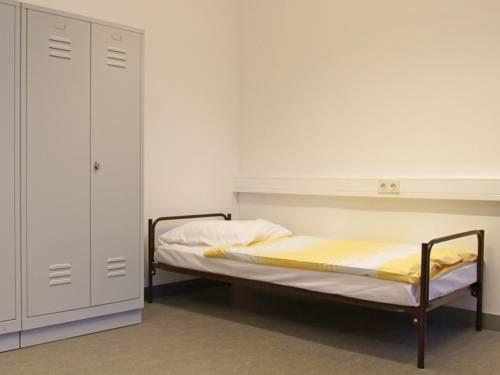 Ein Metallrahmenbett und ein abschließbarer Stahlschrank in einem schmucklosen Raum.