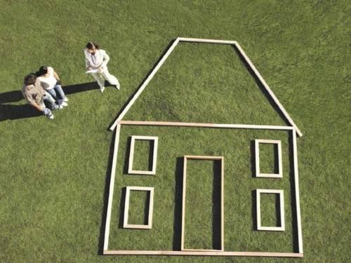 Von oben: Drei Personen auf einer Rasenfläche, auf der die Umrisse eines Hauses gelegt sind.