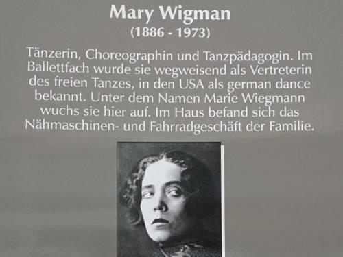 Ausschnitt aus einer Gedenktafel zu Mary Wigman, die ein Portraitfoto einer jungen Frau mit großen Augen zeigt, und biografische Daten auflistet.