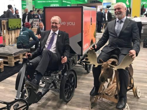 Auf einem Messestand sitzt Oberbürgermeister Schostok auf einem Elektrofahrzeug, daneben Herr Melander aus Göteborg auf einem Holzfahrzeug mit Elch-Geweih.