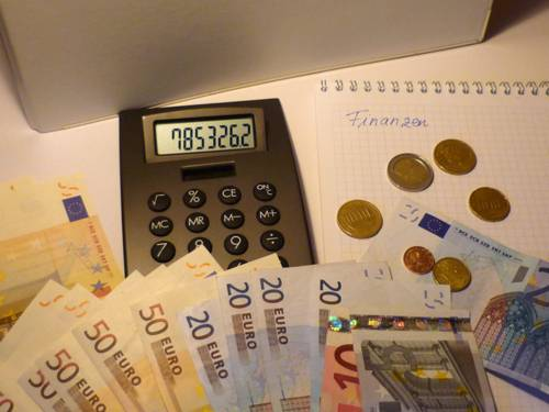 Taschenrechner, der von Geldscheinen und Münzen umrahmt ist.
