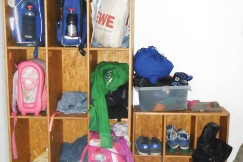 In einem Holzregal sind Rucksäcke und Schuhe von Kindern und Jugendlichen verstaut.