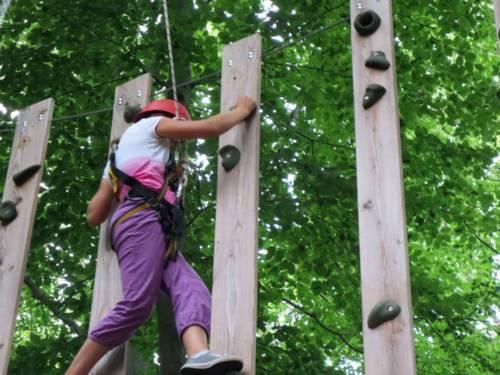 Ein Kind balanciert durch Seile und Helm abgesichert an einer Holzwand