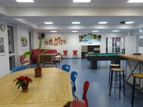 Innenaufnahme vom Jugendzentrum Vinnhorst: Eine Sitzecke, Tisch und Tresen und ein Billiardtisch