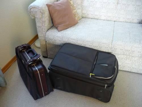 Zwei Koffer neben einem Sofa zeugen von der Ankunft von Gästen