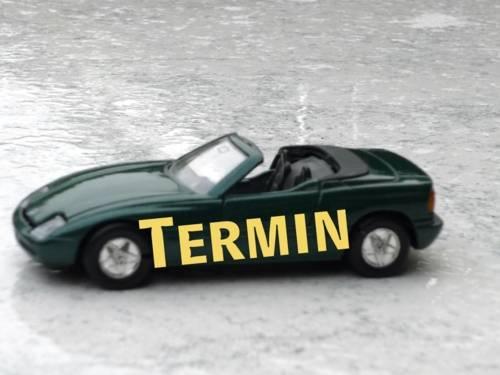 """Grüner Wagen mit Seitenbeschriftung """"Termin"""" auf regennaßem Untergrund"""
