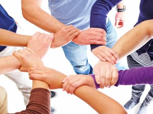Acht Arme von Menschen, die ineinander greifen und sich gegenseitig halten