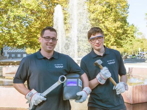 Zwei junge Männer in T-Shirts der Stadtentwässerung halten Schraubschlüssel und Hammer in den Händen.