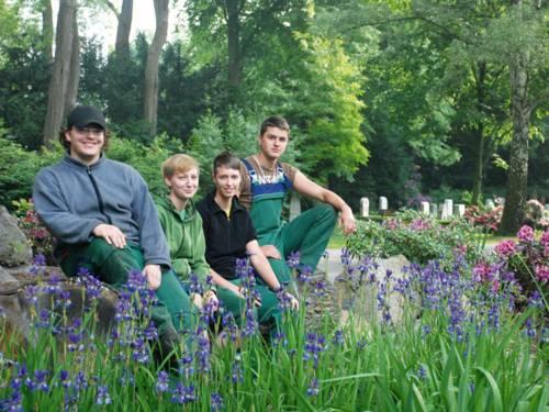 Zwei junge Männer und zwei junge Frauen sitzen in gärtnerischer Arbeitskleidung zwischen blühenden Iris und Rhododendron auf einem städtischen Friedhof