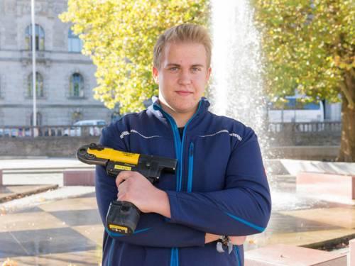 Ein junger Mann in Arbeitskleidung hält ein Arbeitsgerät in der Hand