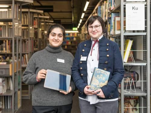 Zwei Auszubildende stehen zwischen Bücherregalen in der Bibliothek - eine hält ein Touch-Pad in der Hand, die andere ein Buch.