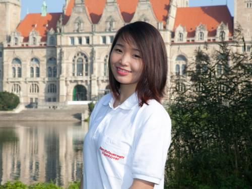 """Junge Frau im weißen Polo-Shirt mit der Aufschrift """"Berufsfeuerwehr Hannover"""" vor dem Rathaus"""