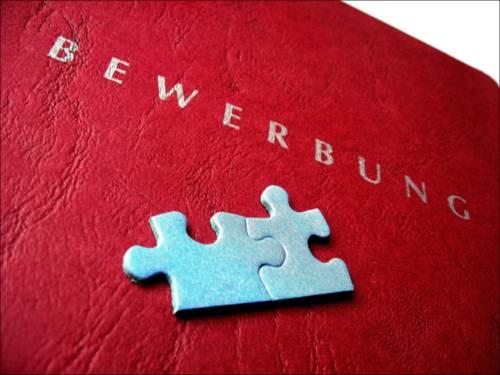 Zwei hellblaue Puzzlestücke liegen auf dem Deckel einer roten Bewerbungsmappe