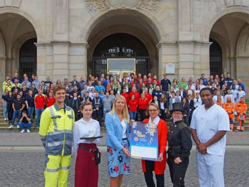 """Eine große Personengruppe steht vor dem Neuen Rathaus Hannover in diverser Berufsbekleidung mit einem Plakat, das für die """"Lange Nacht der Berufe"""" wirbt."""