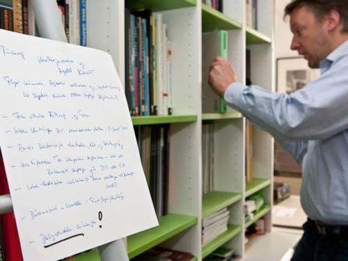 Mitarbeiter an einem Bücherregel mit To-Do-Liste