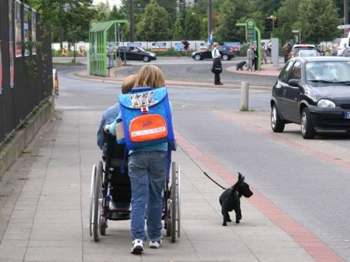 Schulkind schiebt Rollstuhlfahrer und führt einen Hund aus