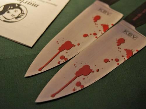 Zwei Messerspitzen mit Bluttropfen, im Hintergrund liegt ein Heft.