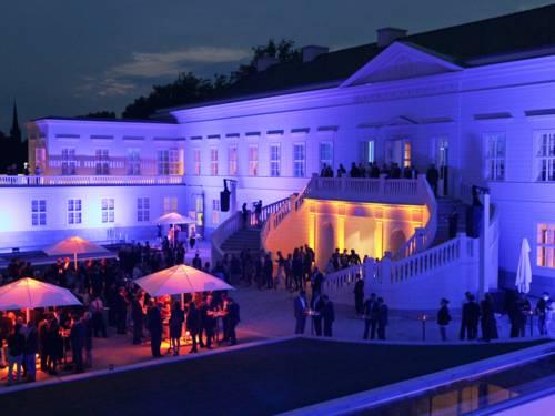 Ein beleuchteter Schlossinnenhof voller Menschen.