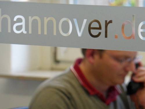 """Schriftzug """"Hannover.de"""" auf einer Glasscheibe, im Hintergrund sitzt ein Mann."""