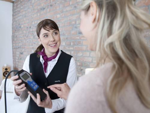 Eine Frau präsentiert einer anderen Frau ein elektrisches Gerät.