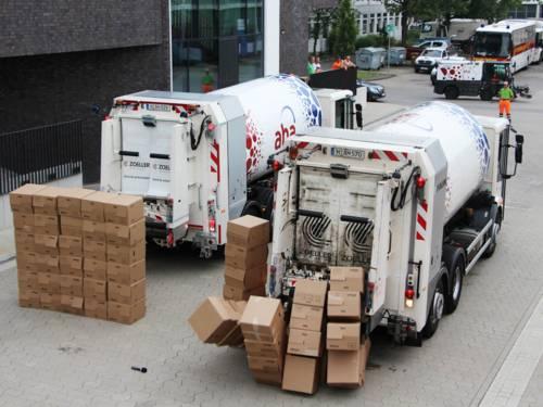 Zwei Müllfahrzeuge von hinten gesehen, eins fährt gegen eine Wand aus Kartons