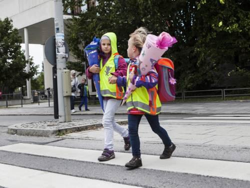 Zwei Kinder mit Schultüten überqueren einen Zebrastreifen