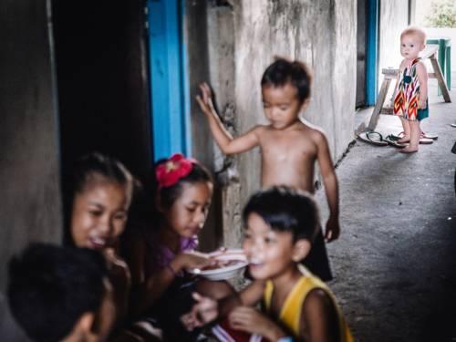 Ein blondes Mädchen beobachtet andere Kinder beim Spielen.