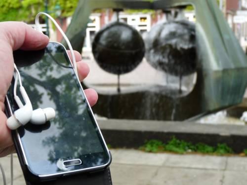 Jemand hält ein Smartphone mit Kopfhörern vor einem Brunnen in der Hand.