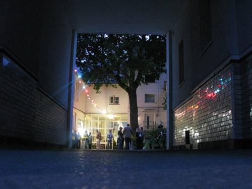 Blick durch eine Durchfahrt in einen Innenhof am Abend. In der Mitte steht ein Baum, unter einer Lichtergirlande stehen Menschen an Stehtischen.