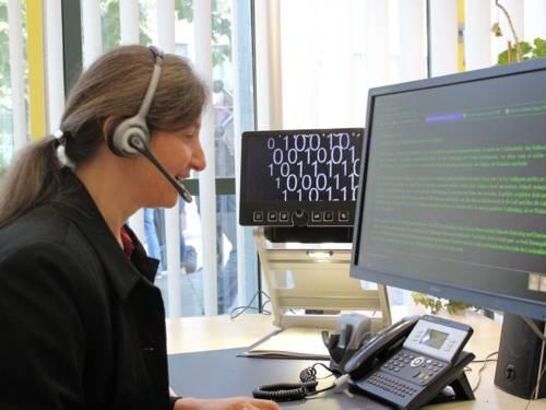 Frau mit Headset vor Bildschirm