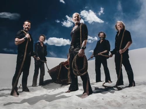 Fünf schwarz gekleidete Männer mit einem Boot im Sand.