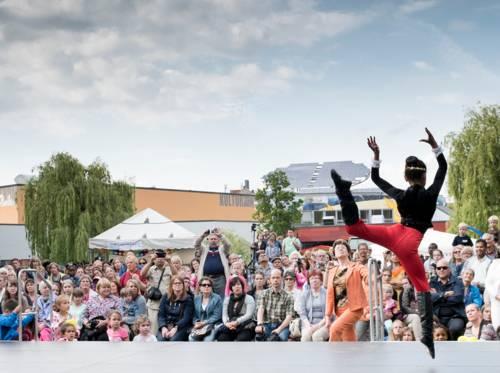 Zuschauer vor einer Bühne und eine Tänzerin auf der Bühne.