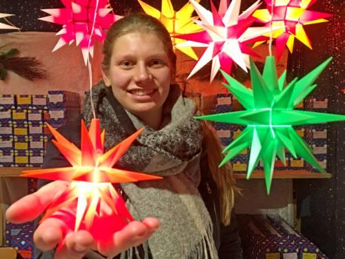 Eine Frau verkauft Herrnhuter Sterne.