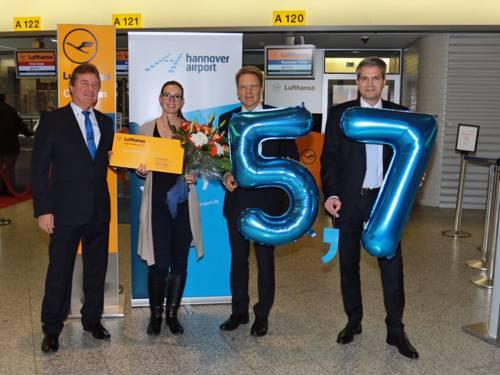 Drei Männer und eine Frau halten Ballons mit den Ziffern fünf und sieben