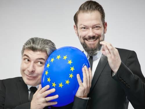 Zwei Männer, einer hält einen Europa-Luftballon, der andere eine Nadel.