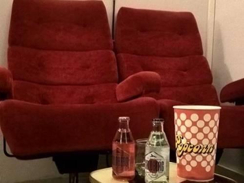 Zwei rote Samtsessel und ein Beistelltisch mit Popcorn.