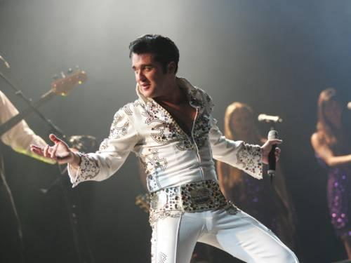 Ein Mann mit weißem Elvis-Kostüm auf der Bühne.