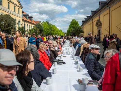 Menschen an einer im Freien gedeckten Kaffeetafel.