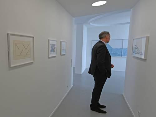 Mann in einem Raum mit Bildern an den Wänden