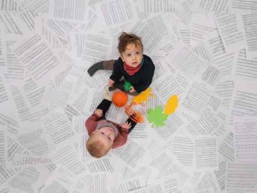 Zwei Babys sitzen auf Notenblättern.