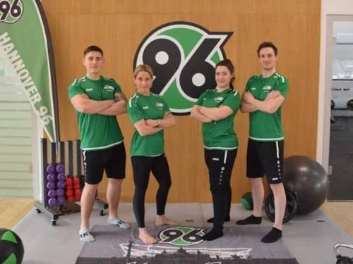 Zwei Frauen und zwei Männer in Sportkleidung