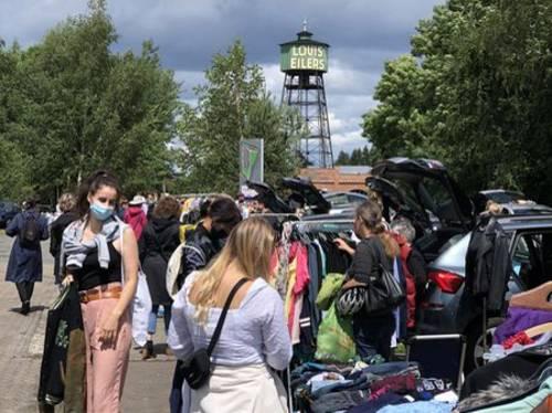 Menschen vor geöffneten und mit Bekleidung gefüllten Auto-Kofferräumen