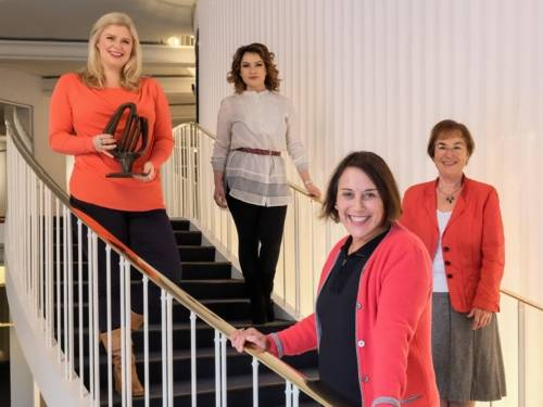 Vier Frauen auf einer Treppe, eine hält eineTrophäe in ihren Händen.