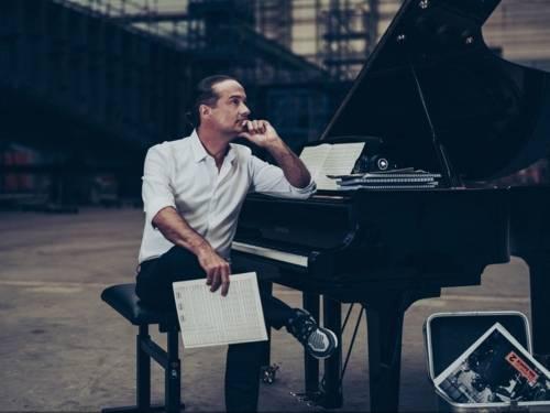 Ein Mann sitzt vor einem Flügel und denkt nach, mit Notenblättern in der Hand.