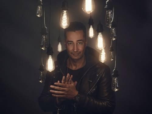 Ein Mann steht zwischen Glühbirnen, die von der Decke hängen. Der Hintergrund ist schwarz und er ist komplett schwarz angezogen.