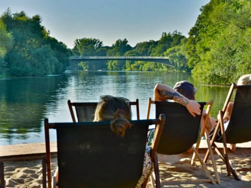Zwei Personen in Sonnestühlen blicken auf eine Brücke über einen Fluss.